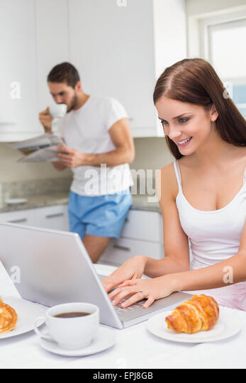 Young woman using laptop at breakfast - Stock Image