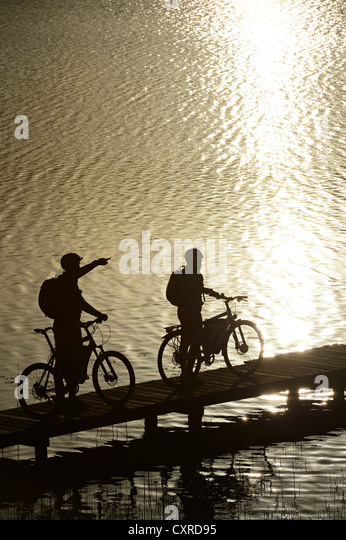 Cyclists with electric bicycles on a jetty, lake at Kloster Seeon Abbey, Chiemgau region, Upper Bavaria, Bavaria - Stock Image