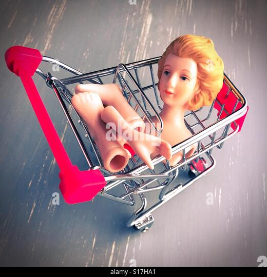 Female doll parts in a shopping cart. - Stock Image