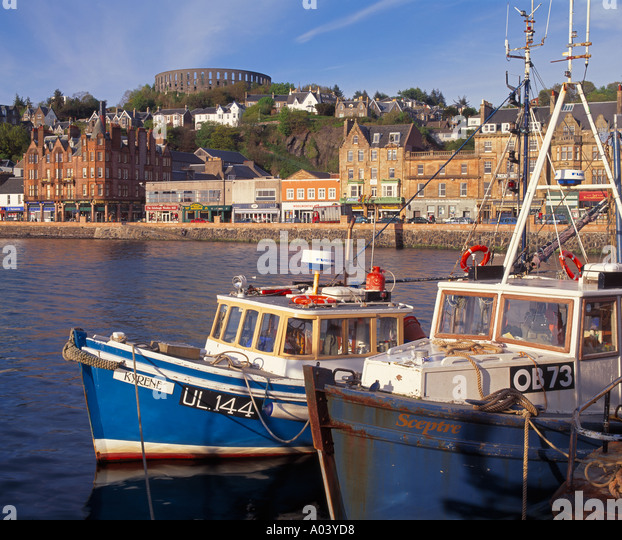 Oban harbour, Argyll and Bute, Scotland, UK.  McCaigs Tower is prominent on the skyline - Stock Image