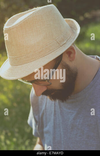 Portrait of a bearded young hipster man daydreaming, looking away. Retro tones - Stock-Bilder