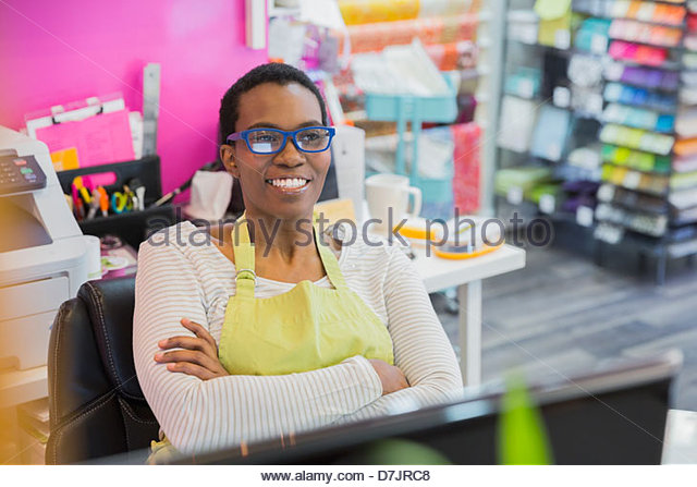 Female small business owner relaxing in store - Stock Image