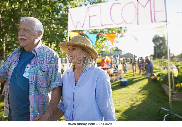 Senior couple leaving neighborhood park party - Stock-Bilder