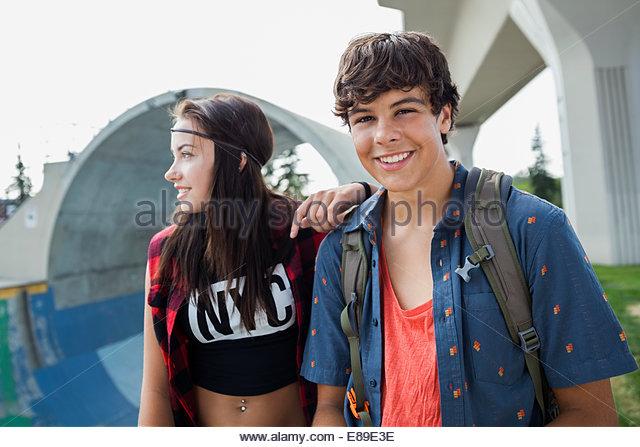 Portrait of smiling teenage couple - Stock Image