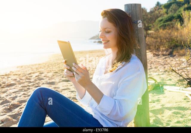 Woman Using a Digital Tablet on the beach - Stock-Bilder