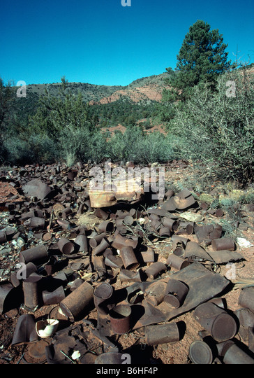 Rusty cans dumped in countryside - Stock Image