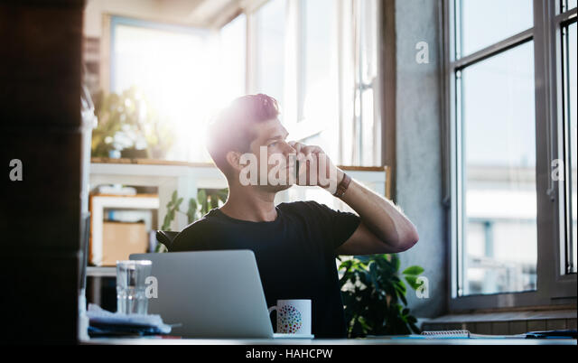 Shot of young man sitting at his office talking on cell phone. Business man working at his desk with laptop making - Stock Image