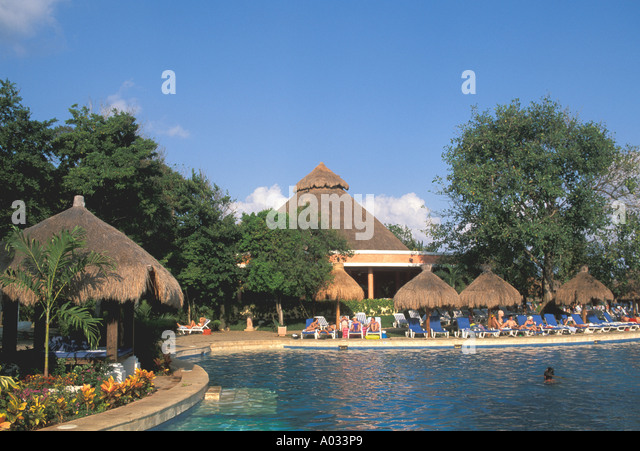Mexico Playa del Carmen resort hotel swimming pool palapa thatch hut relaxing relax - Stock Image