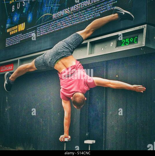 A street gymnast performing in Old Street, London - Stock Image