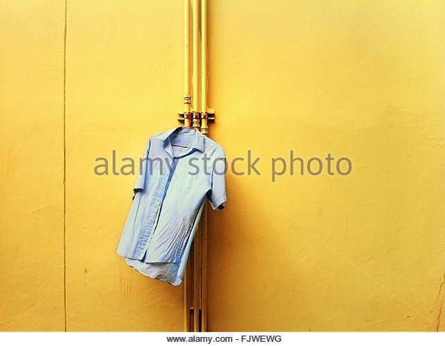 Shirt Drying On Pipe Against Yellow Wall - Stock Image