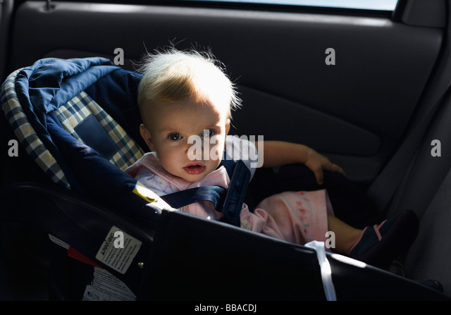 A baby sitting in a car seat - Stock-Bilder