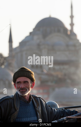Man fishing with Rustem Pasha Mosque in the background, Bosphorus River, Istanbul, Turkey - Stock Image