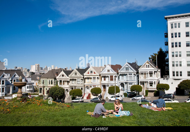 Postcard Row of Painted Ladies Victorian houses from Alamo Square park on Steiner Street, San Francisco - Stock Image