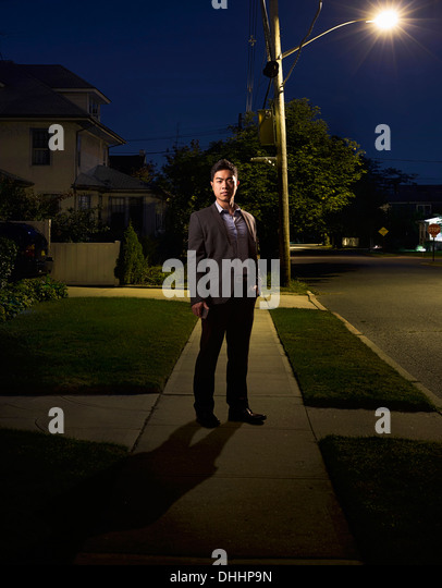 Portrait of business man coming home late at night - Stock-Bilder