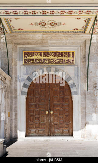 Wooden aged vaulted ornate door and stone wall at Sulaymaniye Mosque, Istanbul, Turkey - Stock Image