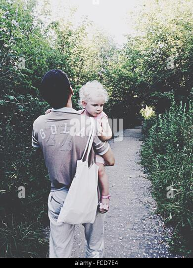 Rear View Of Man Holding Baby And Bag Walking On Walkway Amidst Trees In Park - Stock-Bilder