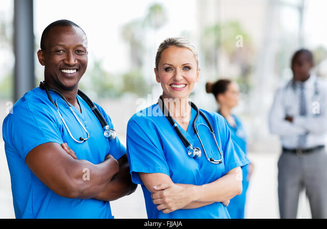 portrait of happy medical co-workers arms crossed - Stock Image