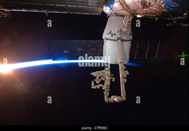 With rays of sunshine and the thin blue atmosphere of Earth serving as a backdrop the SpaceX Dragon commercial cargo - Stock Image
