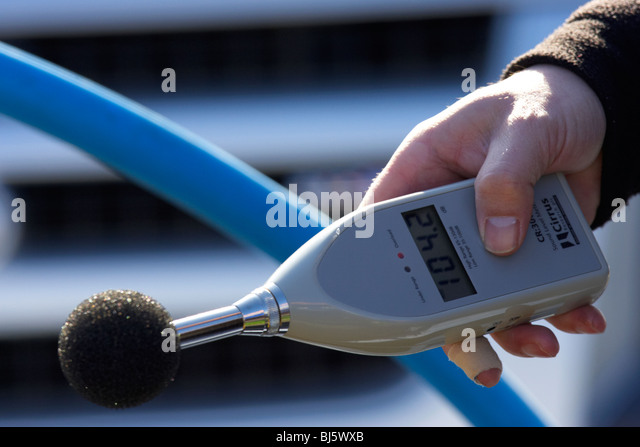 mans hand holding sound level meter with baffle showing measurement of 104.2 dB the meter is used to measure maximum - Stock Image