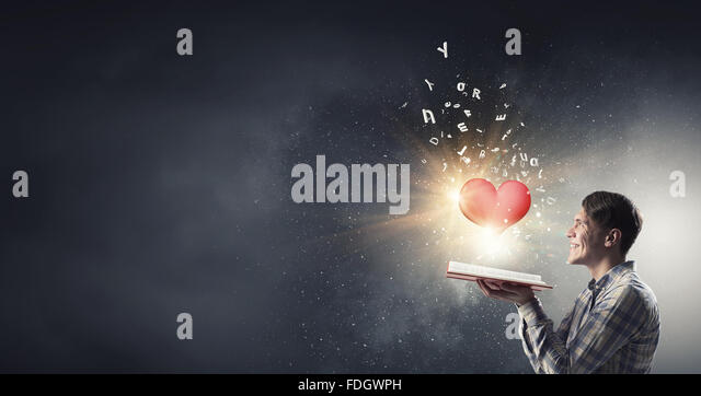 Young man with opened book in hands and red heart on pages - Stock Image