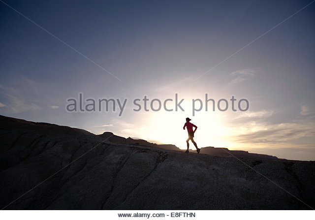 Silhouette of a woman trail running in desert at sunset, Colorado, America, USA - Stock Image