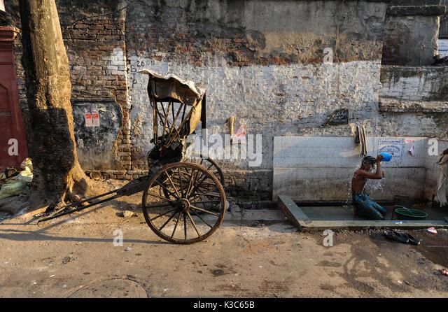 24.02.2011, Kolkata, West Bengal, India, Asia - A rickshaw puller showers next to his wooden rickshaw at a roadside - Stock Image