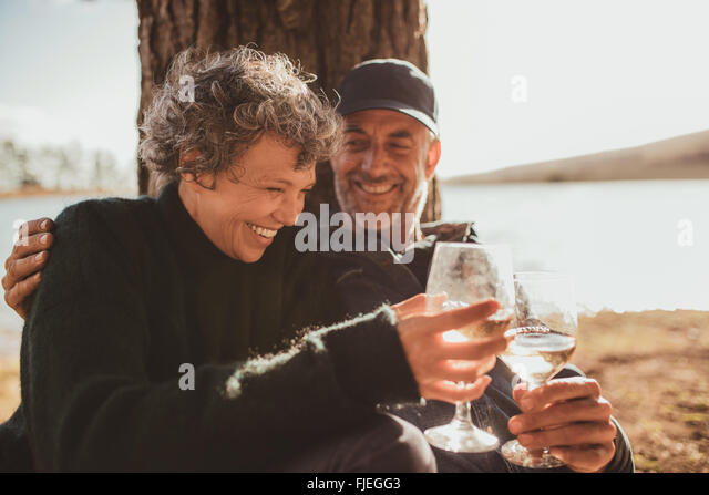 Portrait of relaxed mature couple having a glass of wine at campsite. Senior man and woman toasting wine at on summer - Stock-Bilder