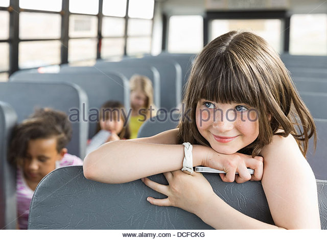Portrait of schoolgirl holding smart phone on bus - Stock-Bilder