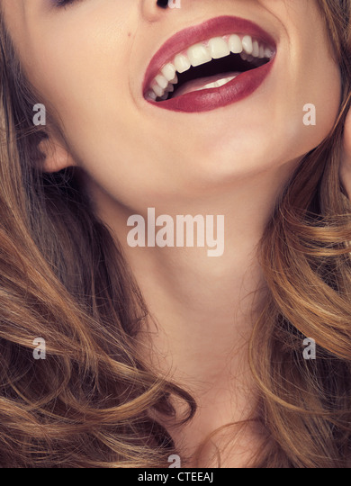 Beautiful young laughing woman closeup of mouth with red lips - Stock Image