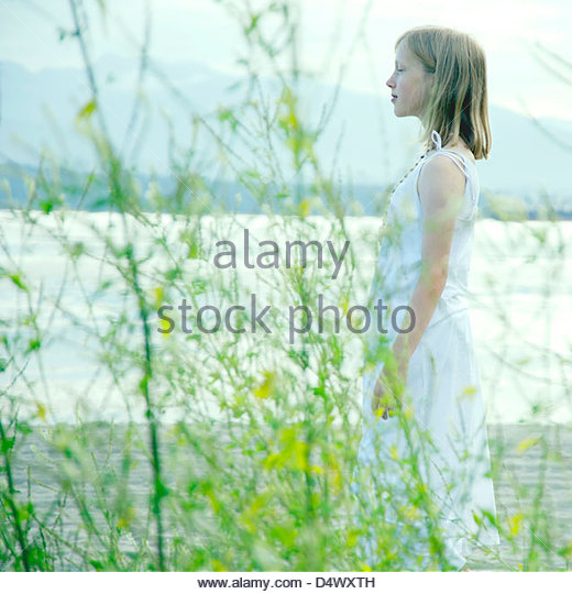 Young girl seen through grasses on the beach standing in meditative pose - Stock Image