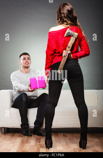 Trusting guy giving present to misleading girl - Stock Image