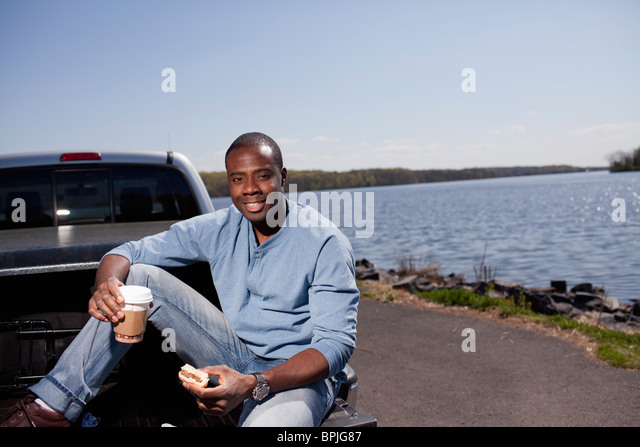 Black man sitting in truck bed eating lunch - Stock Image