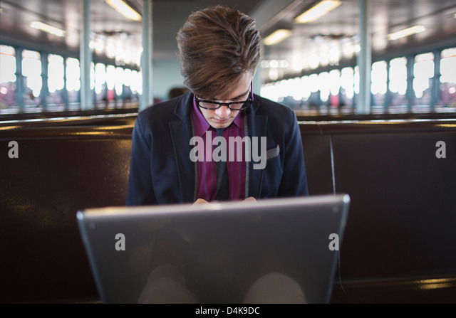 Businessman on laptop in train station - Stock Image