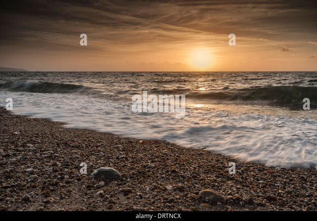 waves washing up the beach over the sand and pebbles at Beesands in Kingsbridge at sunrise on a summers day. - Stock Image