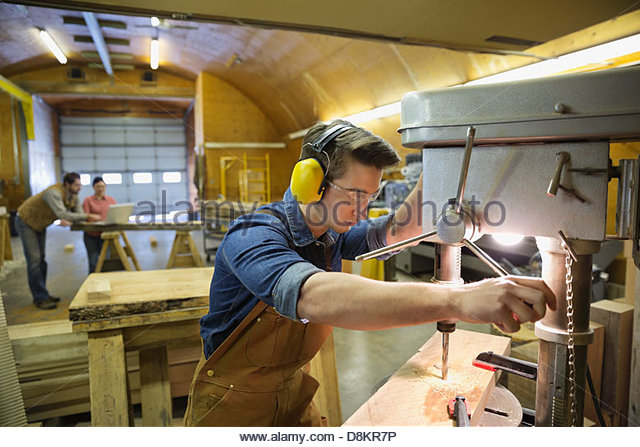 Young male carpenter using drill press in workshop - Stock Image