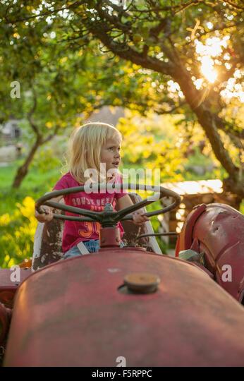 Sweden, Skane, Osterlen, Girl (4-5) on tractor - Stock Image