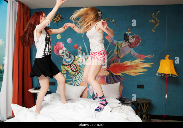 Two young women dancing on hotel bed - Stock Image