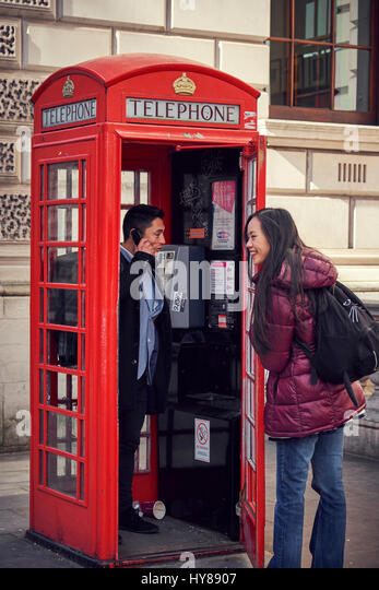 A young Japanese couple make a phone call whilst sightseeing in London - Stock Image