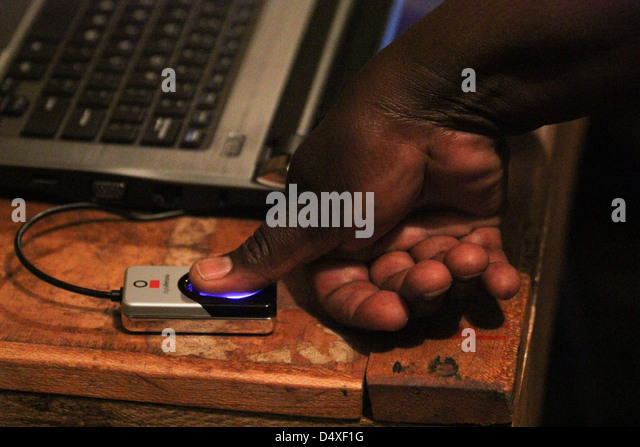 A voter places his thumb on a Biometric Voter registration (BVR) reader at New Kihumbuini Primary School polling - Stock Image
