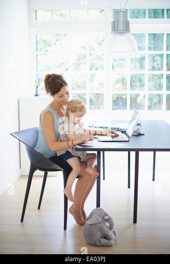 Mid adult woman and toddler daughter typing on laptop - Stock Image