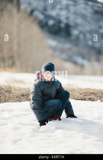 A boy in a blue coat and woolly hat in the snow. - Stock Image