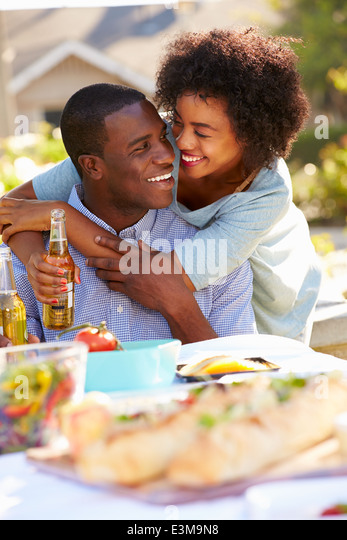 Romantic Couple Enjoying Outdoor Meal In Garden - Stock Image