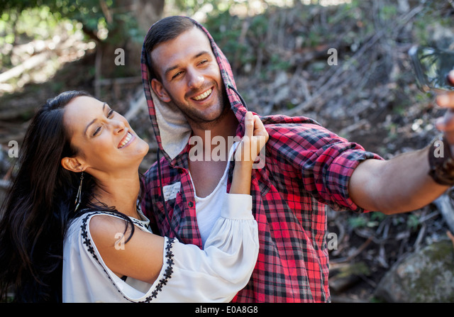 Young couple fooling around in forest - Stock-Bilder