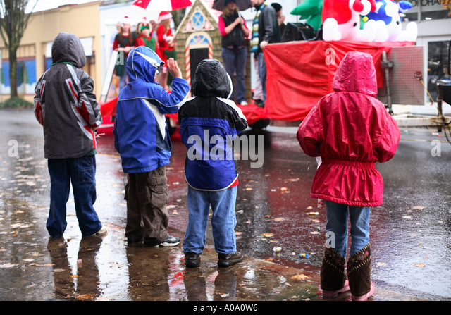 Four children stand in the rain watching a parade - Stock Image