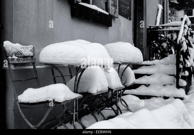 Tables and chairs of a restaurant covered with snow and still snowing, Switzerland. - Stock Image