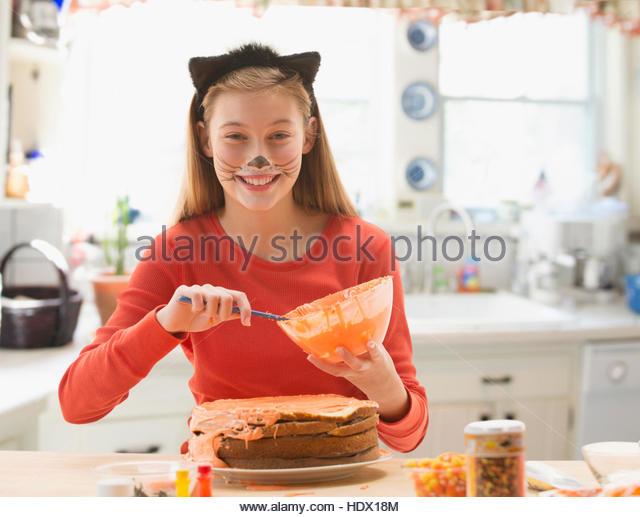 Caucasian girl wearing cat costume spreading icing on halloween cake - Stock Image