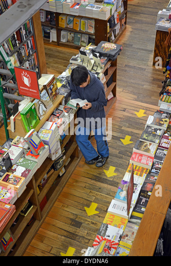 A young Asian man shopping for books at the Strand Bookstore on Broadway in Greenwich Village, Manhattan, New York - Stock Image