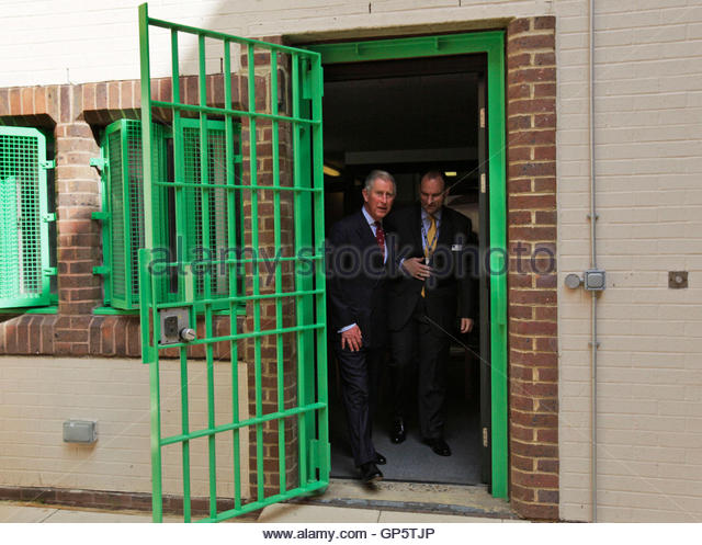 Britain's Prince Charles (L) walks through a gated doorway during a visit to the Belmarsh prison in southeast - Stock Image
