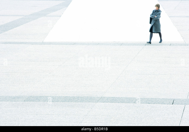 Woman with arms folded walking across city square - Stock Image