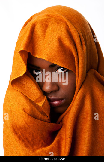 Beautiful mysterious african nomadic bedouin female face in ocher Earth tone head wrap scarf looking. - Stock Image